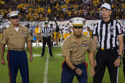 U.S. Marine Corps Col. Terry M. Johnson, center, Commanding Officer, 12th Marine Corps District, tosses the coin during the San Diego State University vs. Arizona State University college football game at San Diego County Credit Union Stadium, San Diego, Sept. 15, 2018. Marines were recognized throughout the duration of the game for their patriotic service.