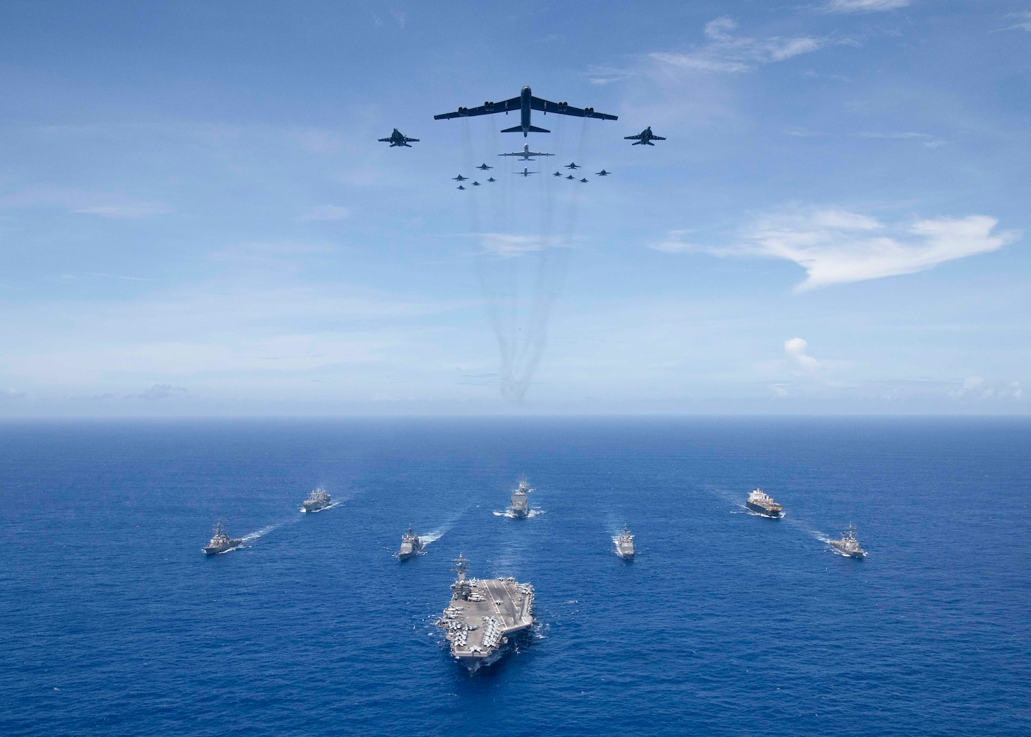 PHILIPPINE SEA (Sept. 17, 2018) USS Ronald Reagan (CVN 76) leads a formation of Carrier Strike Group Five ships as U.S. Air Force B-52 Stratofortress aircraft and U.S. Navy F/A-18s pass overhead for a photo exercise during Valiant Shield 2018. The biennial, U.S. only, field-training exercise focuses on integration of joint training among the U.S. Navy, Air Force and Marine Corps.