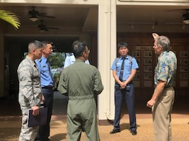 Charles Nicholls, Pacific Air Forces Historian briefs a group of Republic of Korea Air Force  Public Affairs Officers on the air strikes of Dec. 7, 1941 in the Courtyard of Heros at Joint Base Peral Harbor-Hickam, Hawaii on Sept. 11, 2018. ROKAF officers visited PACAF/PA who facilitaed dialogue on the importance of communicating in an integrated, synchronized, and purposeful way to build a united PA system capable of achieving common operational goals in case of emergencies and bilateral operations.  (U.S. Air Force photo by Master Sgt. Nadine Y. Barclay)