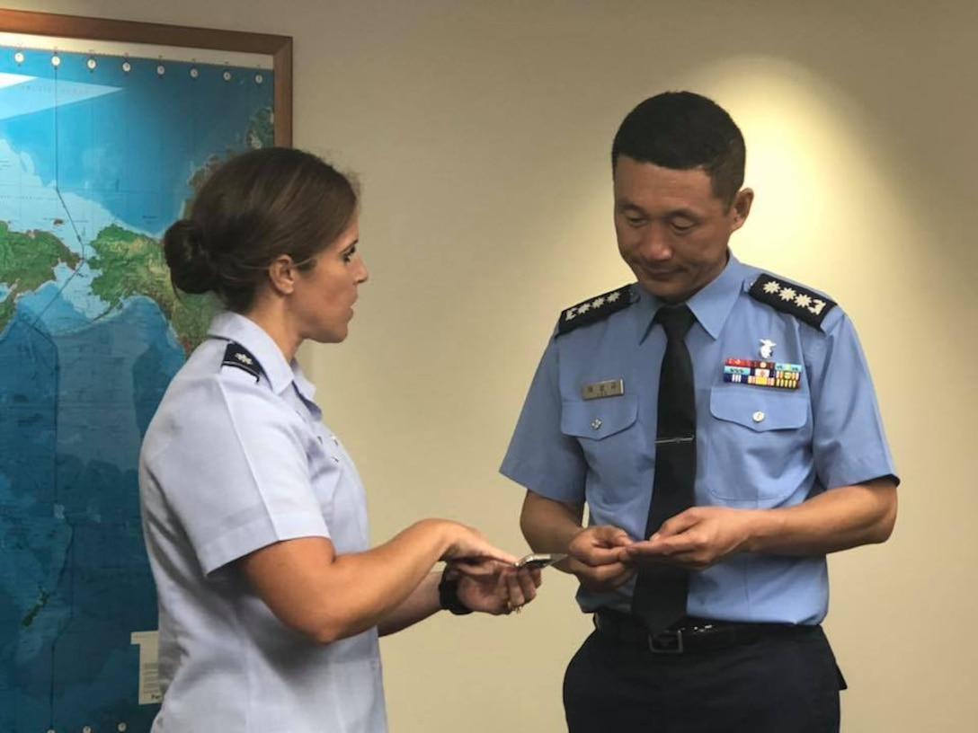 U.S. Air Force Lt. Col. Meagan Schafer exchanges a Pacific Air Forces Public Affairs coin with Republic of Korea Air Force Col. Sang-ky Lee after a meeting aimed at facilitating relationships and dialogue between ROKAF/PA and their U.S. counterparts at Joint Base Pearl Harbor-Hickam, Hawaii Sept. 11, 2018. During the meeting, Lee, also met with professionals from the PACAF/PA, PACAF Band, PACAF Historian, Indo-pacific Command, 7th AF, and the Korean International Affairs Liaison and discussed future ways to engage on the Korean Peninsula. (U.S. Air Force photo by Master Sgt. Nadine Y. Barclay)