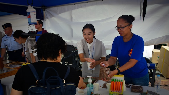 Members of the 51st Aerospace Medicine Squadron Public Health flight and students from local high schools show visitors an U.S. military field ration at the Pyeongtaek Health Festival in Pyeongtaek, Republic of Korea, Sept. 16, 2018.