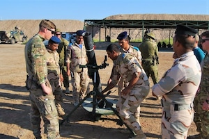 U.S. and Australian army instructors show an Iraqi soldier an M120 mortar system.
