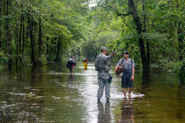 A U.S. Air Force Security Forces Airman assigned to the South Carolina Air National Guard, 169th Fighter Wing, from McEntire Joint National Guard Base, working alongside Florence County, S.C., Sheriff's Department, assists civilians during evacuation efforts as the Black Creek River begins to crest in Florence, S.C., Sept. 17, 2018. Approximately 3,400 Soldiers and Airmen have been mobilized to respond and participate in recovery efforts as Tropical Storm Florence has caused flooding and damage to the state.