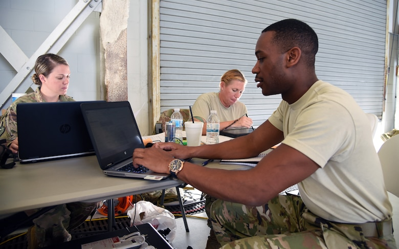 Tech. Sgt. Damon Jones (Jacksonville, Florida), SrA. Alexandra Dubois (Melbourne, Florida) and Master Sgt. Michelle St. Laurent (Melbourne, Florida) track flight times and personnel documents for the 334th Air Expeditionary Group inside the staging hangar at Joint Base Charleston, S.C., Sept. 16, 2018 in support of Hurricane Florence Relief Operations. All three Airmen are forward deployed from the 920th Rescue Wing, at Patrick Air Force Base, Florida. (U.S. Air Force photo/Tech. Sgt. Kelly Goonan)