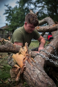 U.S. Marine Corps Lance Cpl. Nicholas A. Johnson with Service Company, Headquarters Regiment, 2nd Marine Logistics Group, hooks up tree branches to be hauled away at Camp Lejeune, N.C., Sept. 17, 2018. Recovery and repair efforts began on base Saturday, September 15, with the majority of efforts focused on clearing roadways and restoring power to critical areas aboard Camp Lejeune following Hurricane Florence. (U.S. Marine Corps photo by Sgt. Bethanie C. Sahms)