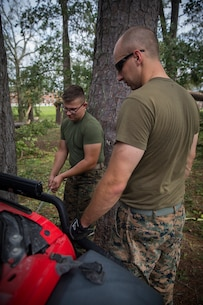 U.S. Navy HM2 Nathaniel Clingerman, left, a hospital corpsman with Battle Skills Training School, Headquarters Regiment (HQ REG), 2nd Marine Logistics Group (2nd MLG), hooks up the winch of his personal vehicle to a broken tree limb at Camp Lejeune, N.C., Sept. 17, 2018. Marines and Sailors of HQ REG organized clean up efforts to remove fallen tree branches and debris from 2nd MLG headquarters and HQ REG buildings. (U.S. Marine Corps photo by Sgt. Bethanie C. Sahms)