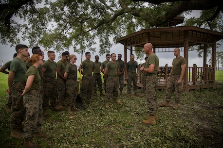 U.S. Marine Corps Sgt. Maj. Steven L. Lunsford, right, sergeant major of 2nd Marine Logistics Group (2nd MLG), speaks to the Marines of Headquarters Regiment (HQ REG), 2nd MLG, during clean up efforts at Camp Lejeune, N.C., Sept. 17, 2018. The Marines assisted clean up efforts by removing debris from 2nd MLG headquarters and HQ REG buildings. (U.S. Marine Corps photo by Sgt. Bethanie C. Sahms)