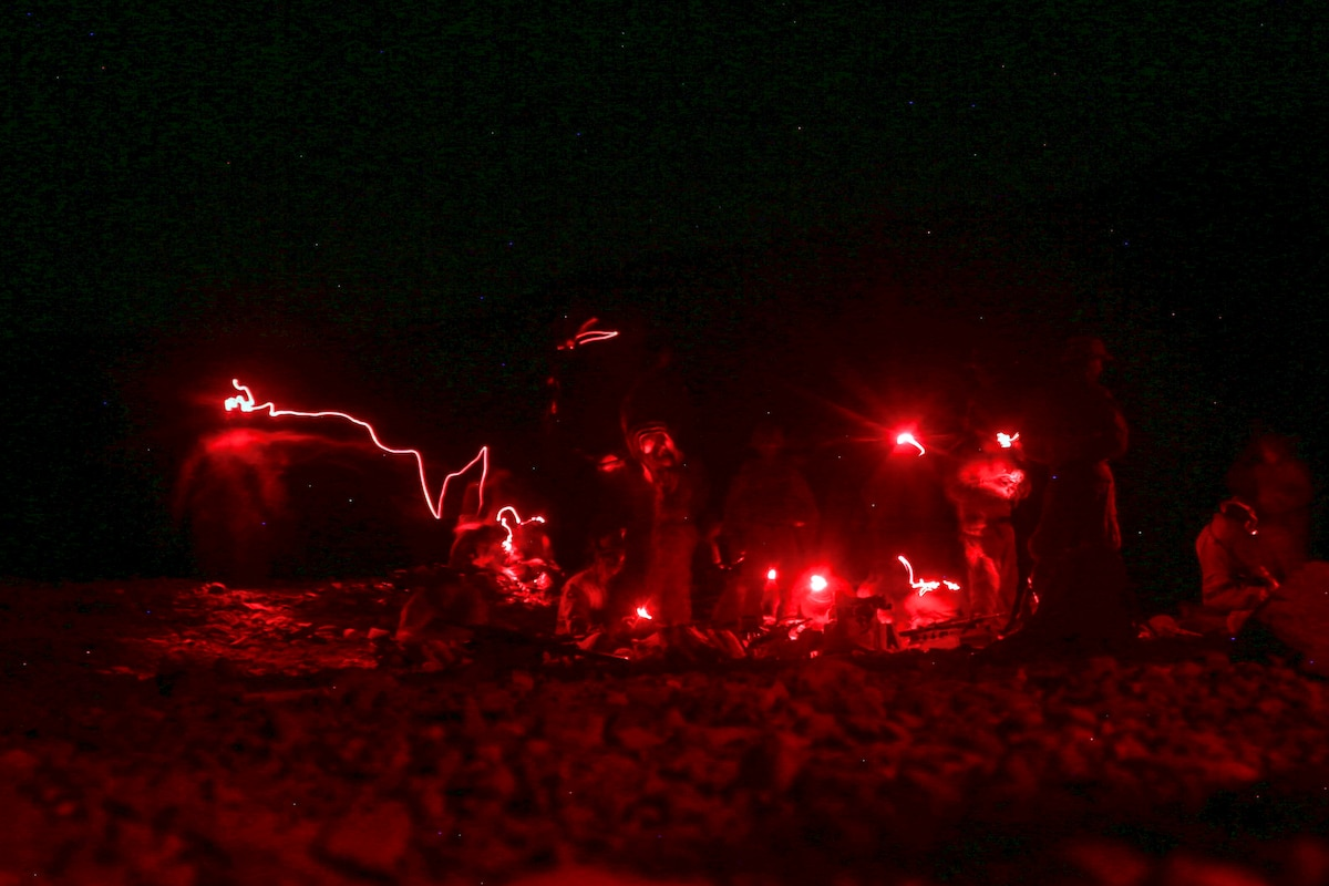Marines load ammunition into magazines for a night live-fire exercise.
