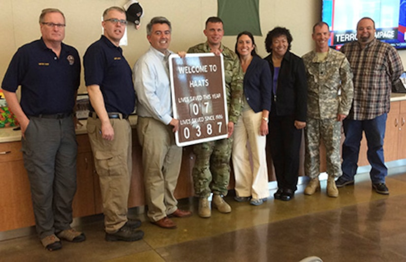 ​U.S. Senator Cory Gardner, third from left, holds the lives saved sign on display at the High-altitude Army National Guard Aviation Training Site in Gypsum, Colo., July 22, 2016. HAATS aircrews provide ground crews hoist capabilities in some of the most unforgiving terrain on earth. Additionally, HAATS aircraft and equipment, such as night vision googles, and extensive crew training allow rescue teams to reach terrain most civilian aircraft cannot. (Photo by defense contractor Michael Hillwig)