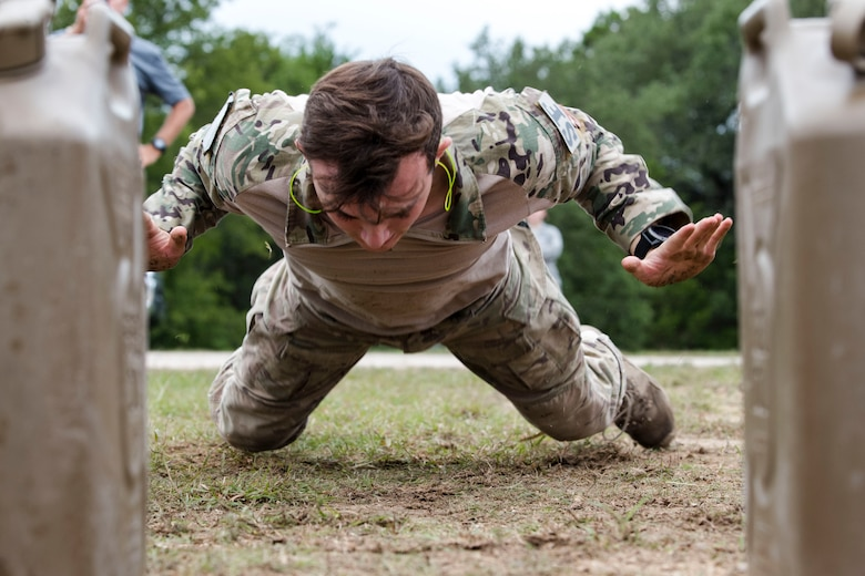 Senior Airman Jeffrey Lewis, 822d Base Defense Squadron fireteam lead, performs burpees during the 2018 Defender Challenge, Sept. 13, at Joint Base San Antonio-Camp Bullis, Texas. Teams representing all twelve Air Force major commands, the Royal Air Force Regiment and German Air Force participated in the friendly competition, which tested their capabilities in dismounted operations, combat endurance and weapons tactics. The ACC team won second place in the overall competition, combat endurance and weapons challenge. (U.S. Air Force photo by Airman Taryn Butler)