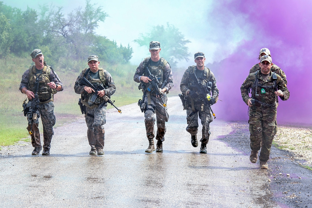 Six airmen carrying weapons jog on a road with purple smoke in the background.
