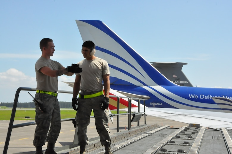 Airmen 1st Class Ryan Adams and Vincent Encinas, air freight technicians from the 730th Air Mobility Squadron offload cargo at Yokota Air Base, Japan before the aircraft continues onto Paya Lebar Air Base in Singapore, 22 Aug. 2018. Air Mobility Command sustains 42 en-route locations around the globe through the use of a complex system of channels. These channels enable transport of personnel and worldwide cargo from location to location to sustain the joint warfighter.