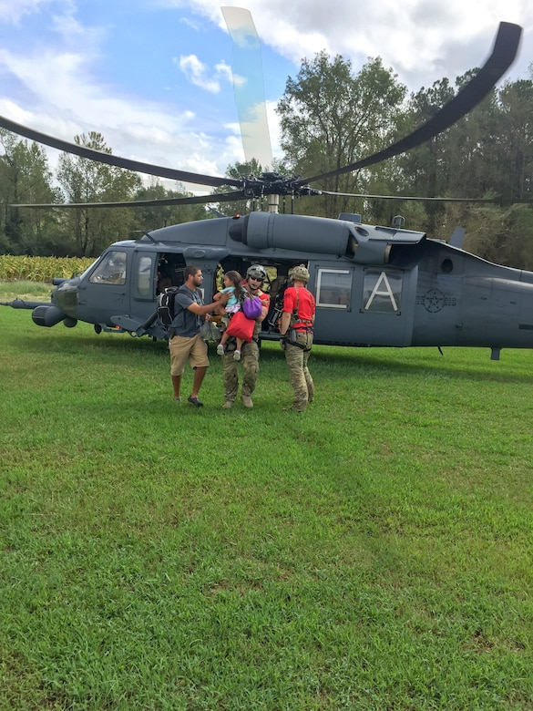 Alaska Air National Guardsmen from the 176th Wing's 212th Rescue Squadron assist with recovering isolated flood survivors via a California ANG's HH-60 Pavehawk helicopter crewed by members of the 210th RQS near Sampson County, N.C., Sept. 17, 2018. (Courtesy photo)