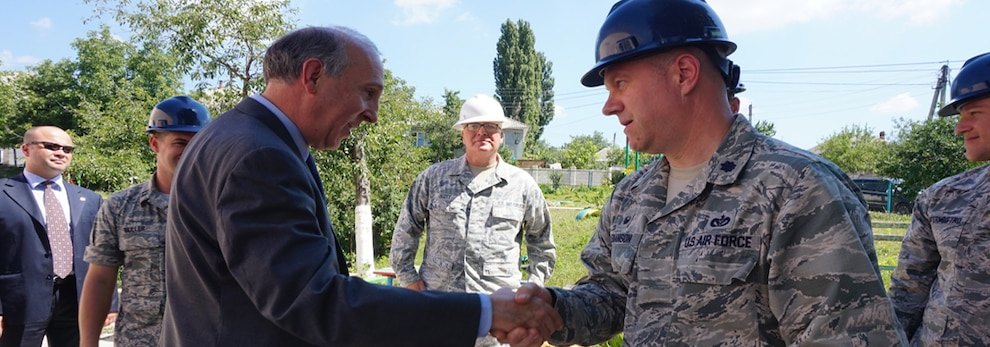 Lt. Col. Eric Swanson, commander of the 113th Civil Engineer Squadron, District of Columbia Air National Guard, greets Jim Pettit, U.S. Ambassador to the Republic of Moldova, during the ambassador's visit to two schools civil engineers renovated as part of a humanitarian civic assistance mission. Since, 1997 the European Command (EUCOM) in cooperation with the Office of Defense Cooperation (ODC) has invested $15 million into similar projects (i.e. schools and clinics) alone in Moldova.