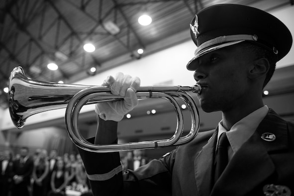 Airman 1st Class Michael Wilson-Jones, 23d Wing Honor Guard drill team member, plays taps to commemorate the Air Force's 71st Birthday during the Air Force Ball, Sept. 15, 2018, at the James H. Rainwater Conference Center in Valdosta, Ga. Moody's Air Force Ball was not only a celebration of the Air Force's 71st Birthday but a way to foster esprit de corps and pride among Airmen through a shared history of exceptional service. (U.S. Air Force photo illustration by Airman 1st Class Erick Requadt)