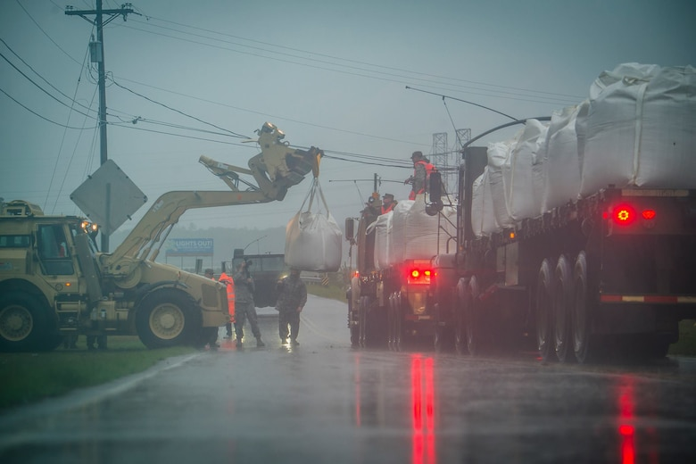 South Carolina Army National Guard Soldiers from the 178th Engineering Battalion and 1050th Transportation Company deliver and unload 1-ton sand bags to deter impending flooding from the Waccamaw River in Conway, S.C., Sept. 15, 2018. (Photo Credit: U.S. Army photo by Sgt. Brian Calhoun)