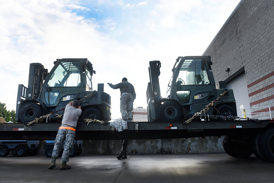 U.S. Air Force Senior Master Sgt. Raymond Graves III (left) and Master Sgt. Barry Boyd (middle), 145th Logistics Readiness Squadron, chain down two forklifts to a flatbed truck at the North Carolina (N.C.) Air National Guard Base, Charlotte Douglas International Airport, Sept.17, 2018.  The forklifts will be used to move pallets filled with supplies like food and water in an attempt to assist in relief efforts associated with Hurricane Florence, and will be transported with an 11-person team to an airport in Kinston, N.C.