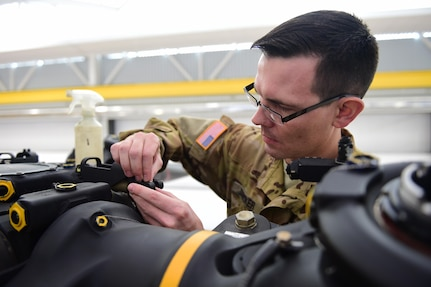 U.S. Army Sgt. Benjamin Stocker, Colorado National Guard CH-47 flight engineer and mechanic, puts a washer into place Feb. 19, 2016, at the Army Aviation Support Facility on Buckley Air Force Base, Colo. As a part of installing a new droop-stop spring, the washer keeps the helicopter blades from falling too low during flights. (U.S. Air Force photo by Airman 1st Class Gabrielle Spradling/Released)