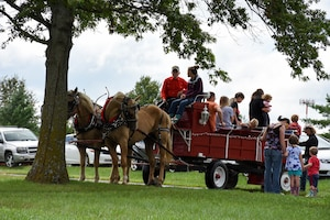 442d Fighter Wing members and their families disembark from a horse-drawn carriage at the 442 FW Family Day event Sept. 9, 2018, at Ike Skelton park on Whiteman Air Force Base, Mo.