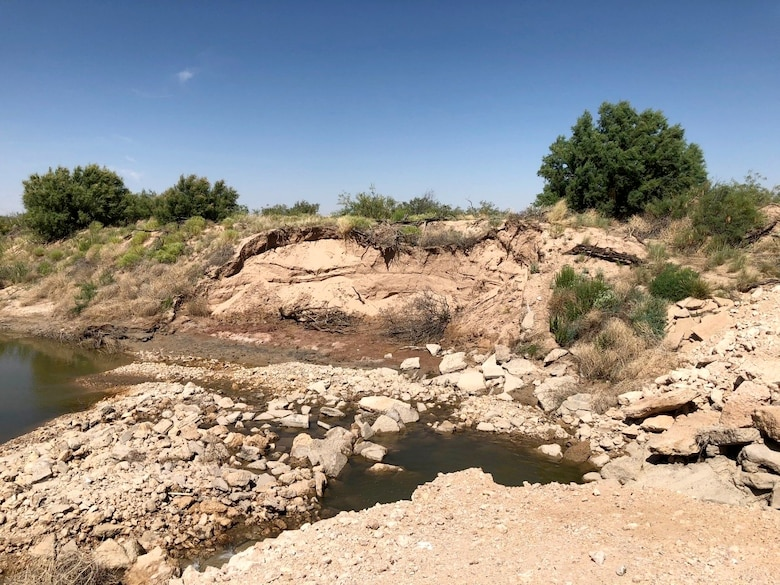 The unauthorized dam failed and caused significant erosion on the west side of the river.