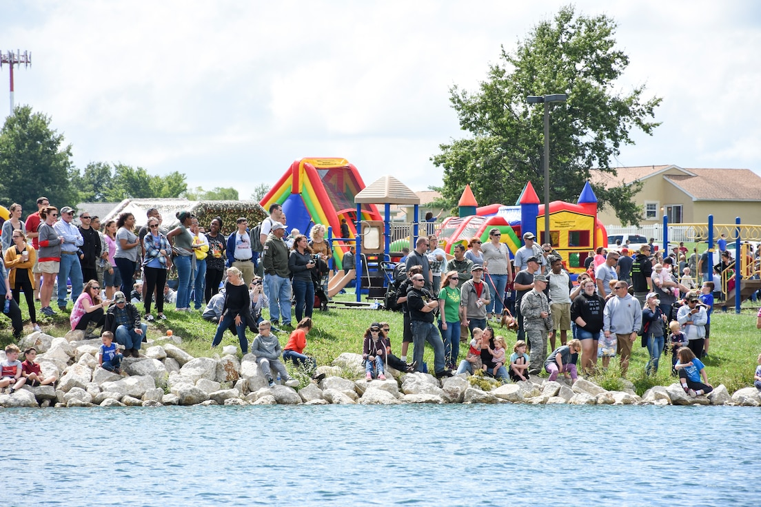 A crowd watches the carboard boats get lowered into the water for the 442d Fighter Wing Family Day Cardboard Regatta Sept. 9, 2018, at Ike Skelton Park on Whiteman Air Force Base, Mo.