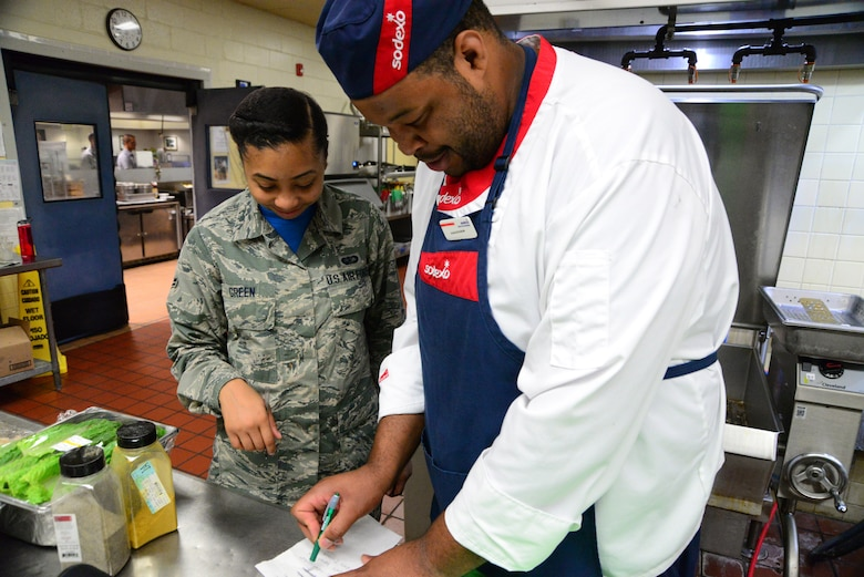 Airman 1st Class Iyana Green (left), 436th Force Support Squadron food service apprentice, and Hassan Amenu-el, line cook, ensure they meet their objectives for the morning preparation Sept. 14, 2018, at the Patterson Dining Facility on Dover Air Force Base, Del. The civilians and Airmen have a policy of transparency and communication to improve team efficiency and cohesion. (U.S. Air Force photo by Airman 1st Class Dedan Dials)
