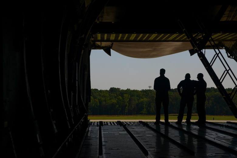 Members look out the tail end of a C-5M Super Galaxy assigned to the 3rd Airlift Squadron Sept. 5, 2018. Marine Corps Systems Command land systems defense acquisition engineers and logisiticans visited Dover AFB to develop ideas on how to better assist with loadmaster capabilities. (U.S. Air Force photo by Airman 1st Class Jonathan Harding)