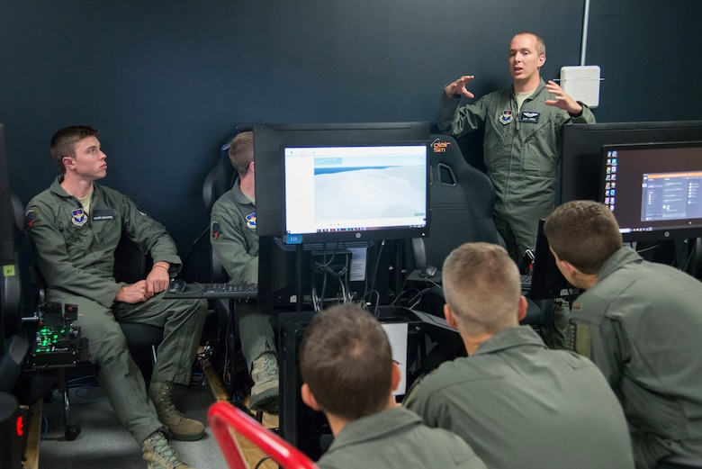 U.S. Air Force Capt. Johnathan Joern (standing), Pilot Training Next instructor pilot, trains PTN students on flying procedures at the Armed Forces Reserve Center in Austin, Texas, June 22, 2018. Air Education and Training Command officials announced the second iteration of Pilot Training Next would begin in January 2019 during a panel at the 2018 Air Force Association Air, Space and Cyber Conference in National Harbor, Maryland. (U.S. Air Force photo by Sean M. Worrell)