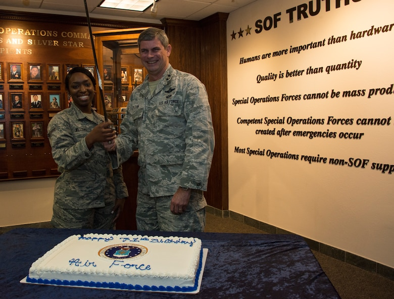 Two people in front of a cake on a table.