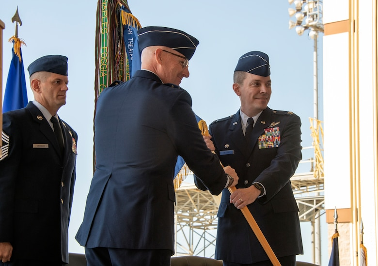 Maj. Gen. Sam Barrett, 18th Air Force commander, passes the 60th Air Mobility Wing guidon to Col. Jeff Nelson, 60th Air Mobility Wing commander, during an assumption of command ceremony at Travis Air Force Base, Calif., Sept. 18, 2018. During the ceremony, Nelson assumed command of Air Mobility Command's largest wing. (U.S. Air Force photo by Lan Kim)
