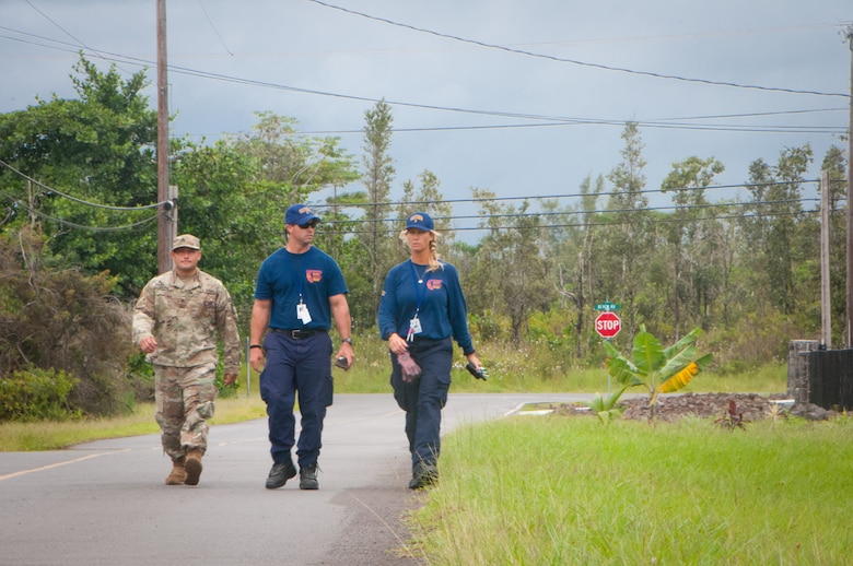 Staff Sgt. William Muira, from the Hawaii National Guard's CBRNE Enhanced Response Force Package (CERFP) Team, escorts FEMA Urban Search and Rescue members from California Task Force 3 while they perform a wide area assessment in the wake of Hurricane Lane