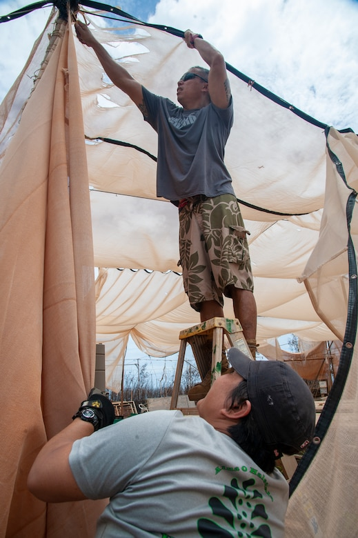 1st Sgt. Marlon Domingo (top) with the 230th Engineering Battalion secures canvas on a damaged aquapponics structure while wife, Master Sgt. Shannon Domingo with the 292nd Combat Communications Squadron secures the ladder at Lahainaluna High School