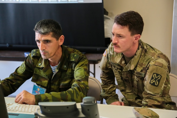 Utah Army National Guard Spec. Chanson Hardy (right) and a Tajik National Army officer evaluate a scenario during command post exercise Regional Cooperation 18 (RC18) at Camp Edwards on Joint Base Cape Cod, Massachusetts, Sept. 15, 2018. Regional Cooperation is an annual exercise conducted by multiple national partners that strengthens military-to-military relationships between U.S. forces and nations in Central and South Asia.  The exercise enhances regional security and stability by exercising a response to current regional security concerns. (U.S. Central Command Public Affairs photo by Tom Gagnier)