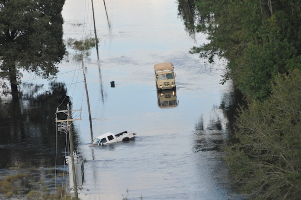 A U.S. Army high clearance vehicle makes its way to a stranded pick up truck on a flooded roadway near Nichols, South Carolina, Sept. 18, 2018.