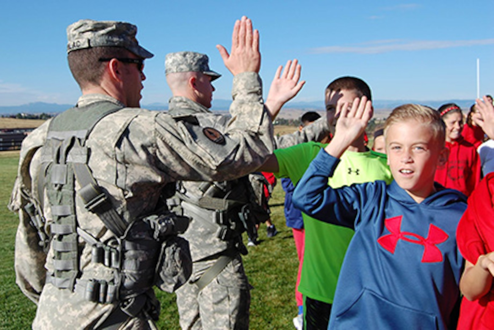 Chief Warrant Officer 2 Marc Kudlac, UH-60 pilot, and Sgt. Sam Groff, UH-60 crew chief, Colorado Army National Guard, high-five students at Cimarron Middle School during a Red Ribbon Week school visit. The Colorado National Guard's Joint Counterdrug Task Force conducts almost a hundred visits like this over the course of each year in an effort to inspire kids in Colorado to stay drug-free.