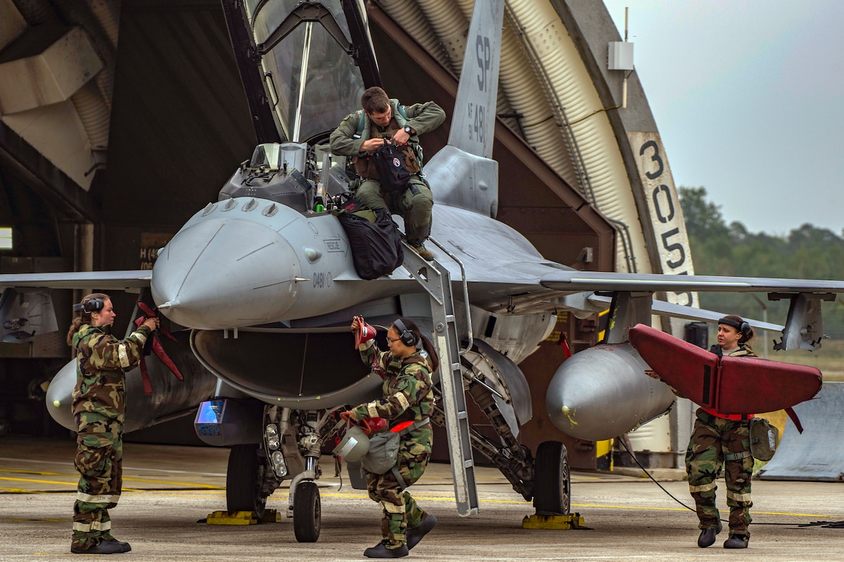 An airman disembarks from an F-16 Fighting Falcon.
