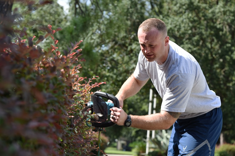 U.S. Air Force Tech. Sgt. Zachary Koeller, Mathies NCO Academy student, trims hedges outside the academy at Keesler Air Force Base, Mississippi, Sept. 18, 2018. In order to assist base operations support, Keesler Airmen will provide grounds maintenance around their work area. (U.S. Air Force photo by Kemberly Groue)