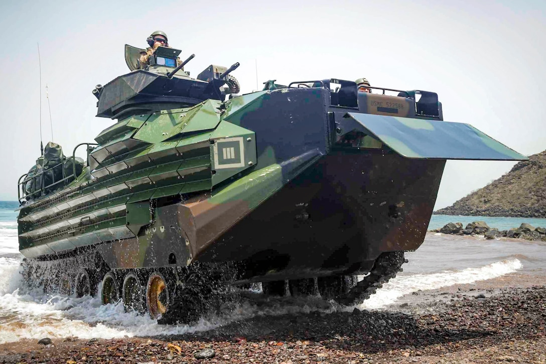 Marines drive onto the shore in an amphibious vehicle.