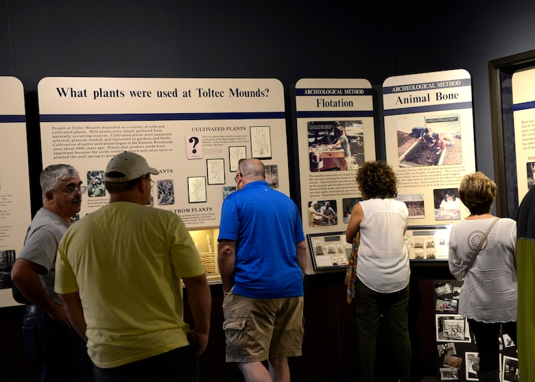 A group of white females and males look at displays at a museum.