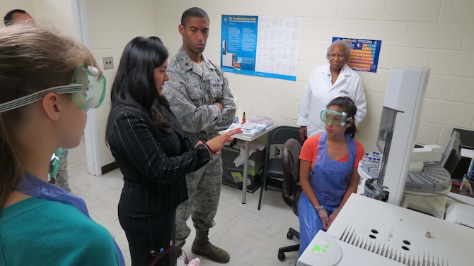 Diana Velosa (center, in black) a chemist with the Air Force Technical Applications Center, provides mentorship to Dayana Paz (seated) during the June 2015 STEMversity program on the campus of Central State Hospital in Georgia.  Velosa and fellow AFTAC member Maj. Allen Cohen (pictured), attended the summer program that focuses on STEM and gives underrepresented middle and high school youth an opportunity to conduct experiments and use precision instruments in real-life laboratories.  (U.S. Air Force photo by Rose Day)