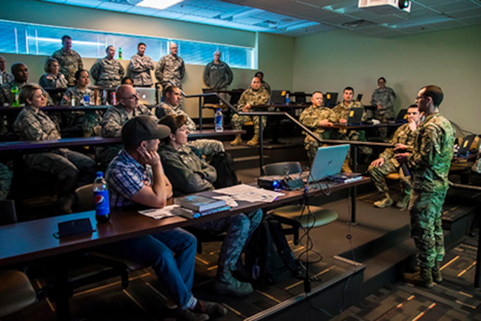 Chief Warrant Officer 2 Adam Johnston, of the Colorado National Guard's Defensive Cyber Operations Element, provides a briefing to the Joint Task Force - Centennial, about what the Vital Connection cyber exercise tests for and the overall process, at the Regis University training center in Greenwood Village, Colo., Feb. 12, 2017. (U.S. Air National Guard Photo by Maj. Darin Overstreet)