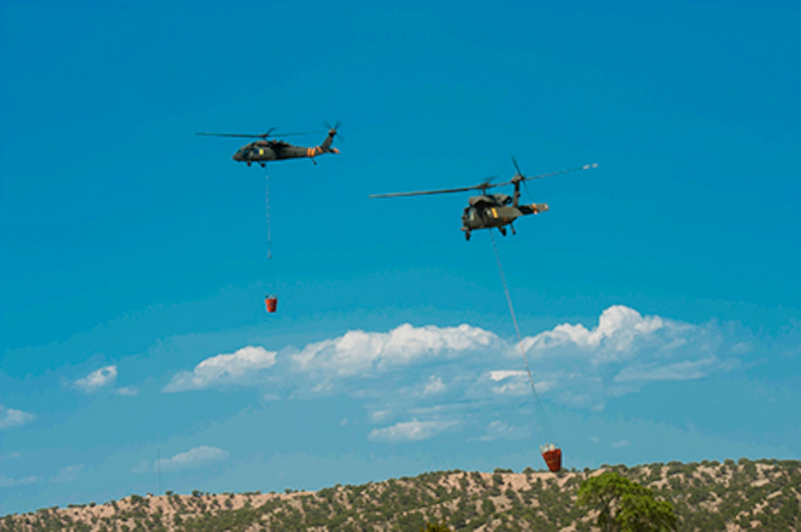 Two UH-60 Black Hawk helicopter crews with aircraft, equipped with aerial water buckets, from the Chief Warrant Officer 5 David R. Carter Army Aviation Support Facility based at Buckley Air Force Base, Aurora, Colorado, depart the Spring Fire helibase, in Fort Garland, Colo., to support fire suppression efforts July 3, 2018. The team arrived and began operations July 2.  The CONG has supported the Spring Fire since July 1, 2018, providing capabilities to include: security personnel for traffic control points and roving patrols; two UH-60 Black Hawk helicopter crews and aircraft each equipped with aerial water buckets; geological information system operators; as well as, refueling crews with Heavy Expanded Mobility Tactical refueling trucks and firefighters with HEMTT firefighting vehicles.  The CONG has been providing an aviation search and rescue standby capability in support of the Rocky Mountain Area Coordination Center since July 1. The High-Altitude Army National Guard Aviation Training Site facility in Gypsum, Colorado, is supporting the mission which is rapid response to aviation search and rescue missions, primarily for firefighter safety, in support of multiple wildfire responses throughout Colorado.  On order of the Governor, the standing Joint Task Force - Centennial commands and integrates CONG forces to support civil authorities in assisting Colorado, or supported states, during times of crisis and disaster, to save lives, prevent suffering, and mitigate great property damage.  (U.S. Air National Guard photo by Tech. Sgt. Nicole Manzanares)