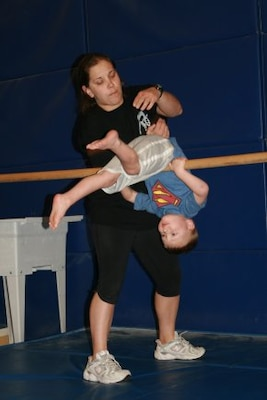 Gymnastics Instructor Jillian Frank helps 3-year-old Colton Taylor flip over a bar during a gymnastics class April 2, 2012 at Fort Carson, Colo. Taylor battled a rare form of cancer for more than two years, but now participates in the activities most children his age enjoy. (Photo credit: For Carson Public Affairs)