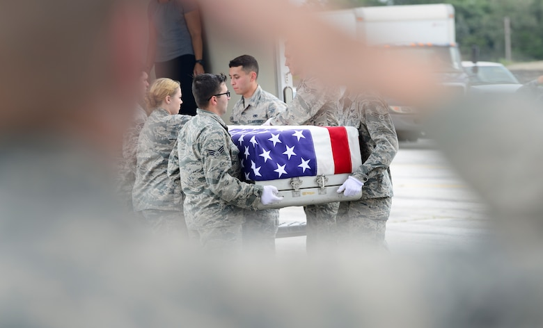 Attendees salute the remains of WWII heroes as they are moved during a flight line ceremony Sept. 14, 2018, at Offutt Air Force Base, Nebraska. Aircrew from Joint Base Charleston, S.C. was tasked to deliver the remains due to its rapid mobility capabilities.