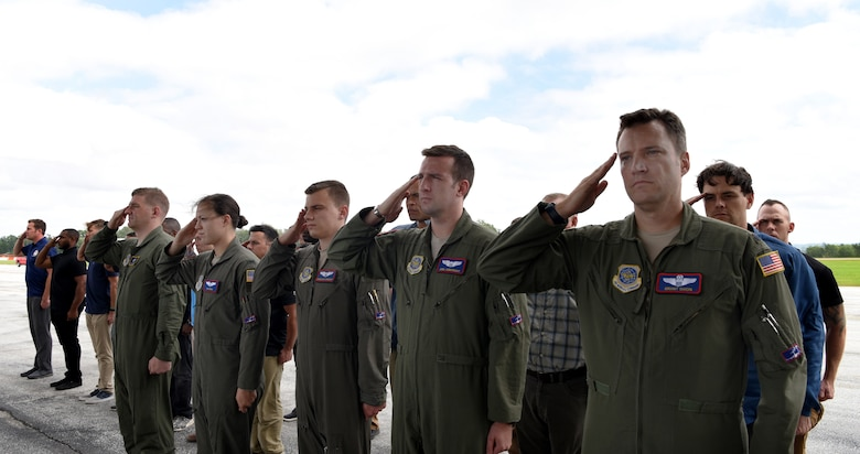 The aircrew salute the remains of WWII heroes as they pass during a flight line ceremony Sept. 14, 2018, at Offutt Air Force Base, Nebraska. Aircrew from Joint Base Charleston, S.C. was tasked to deliver the remains due to its rapid mobility capabilities.