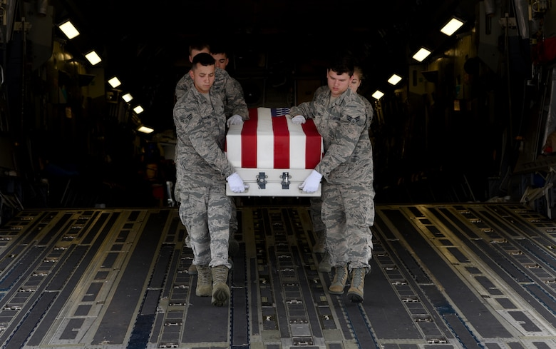 Members of the honor guard carry a transfer case off of a C-17 Globemaster III during a repatriation ceremony of 26 WWII human remains Sept. 14, 2018, at Offutt Air Force Base, Nebraska. Aircrew from Joint Base Charleston, S.C. was tasked to deliver the remains due to its rapid mobility capabilites