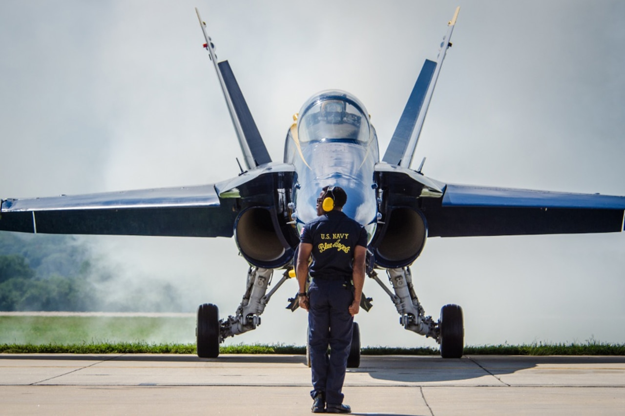 An airman stands in front of a jet.