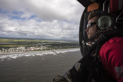 A pararescueman assigned to the 334th Air Expeditionary Group scans the coastline, Sept. 16, 2018, in the skies over South Carolina. The 334th AEG is an expeditionary search and rescue unit, which is pre-positioned to provide relief in the wake of tropical storm Florence. Comprised of 23d Wing and 920th Rescue Wing personnel and assets, the 334th AEG is ready to perform surface, fixed wing and rotary SAR operations when needed.