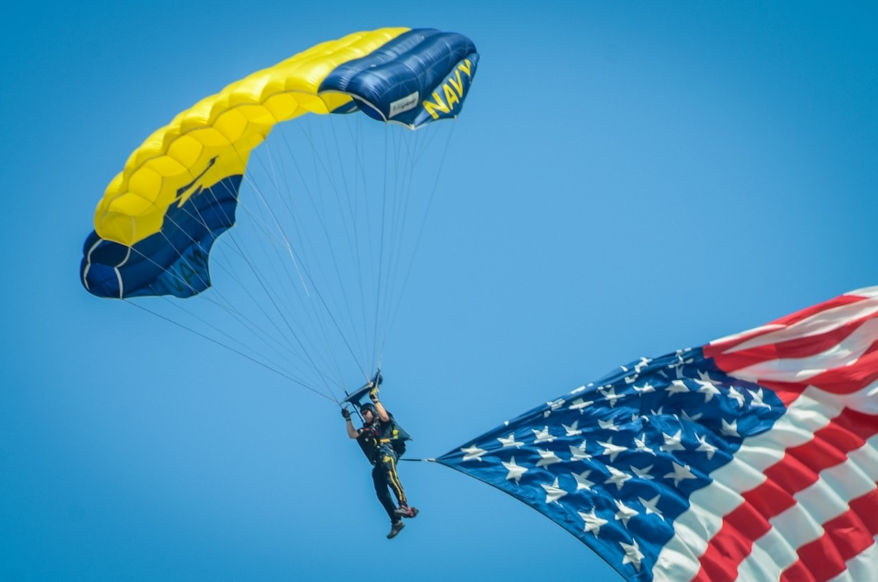 A man parachutes with a flag attached to him.