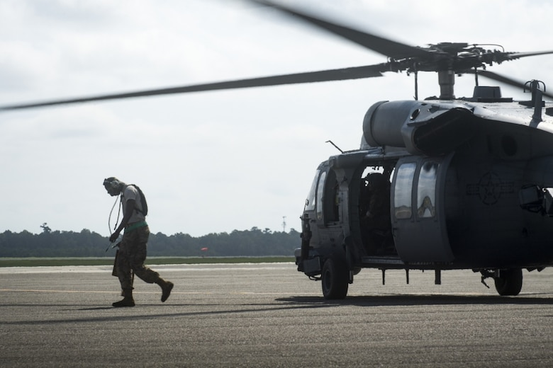Senior Airman Marlon Natty, 334th Air Expeditionary Group crew chief, pulls the chocks from under an HH-60G Pave Hawk as it prepares for an area familiarization flight, Sept. 17, 2018, at Joint Base Charleston, S.C. The 334th AEG is an expeditionary search and rescue unit, which is pre-positioned to provide relief in the wake of tropical storm Florence. Comprised of 23d Wing and 920th Rescue Wing personnel and assets, the 334th AEG is ready to perform surface, fixed wing and rotary SAR operations if called upon.
